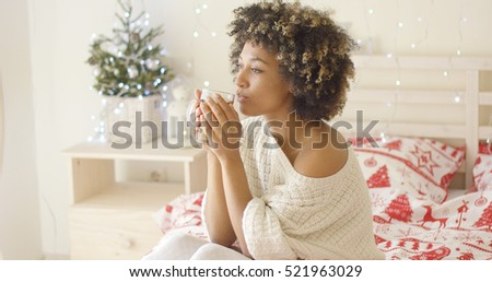 Calm adult in sweater sipping tea while in bed