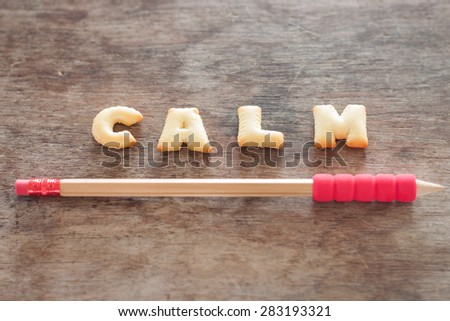 Calm alphabet biscuit on wooden table, stock photo - stock photo