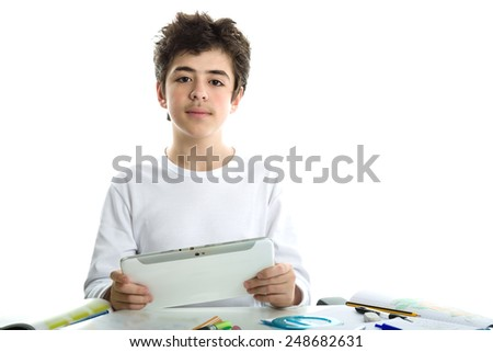 Calm and confident Caucasian smooth-skinned boy wearing a white long sleeve t-shirt is holding a tablet computer on homework - stock photo