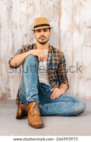 Calm and confident. Handsome young man wearing hat and looking at camera while sitting against the wooden wall  - stock photo