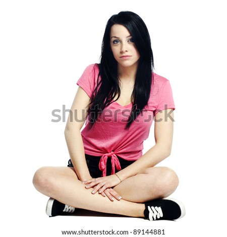 Calm and confident young woman with edgy look sitting down - stock photo