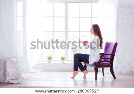 Calm and coziness. Beautiful young woman with cup of tea sitting on armchair at home. - stock photo