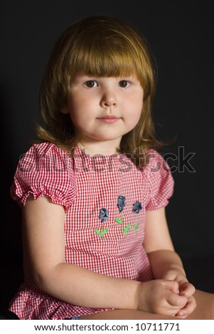 Calm and kind little girl in pink blouse over black background
