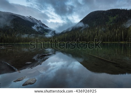 Calm and Peaceful view with the reflection on the lake during a cloudy sunset. Taken at Joffre Lake, BC, Canada. - stock photo