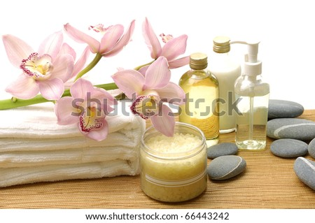 Calm and relaxing spa setting with orchid on towel with massage oil and stone - stock photo