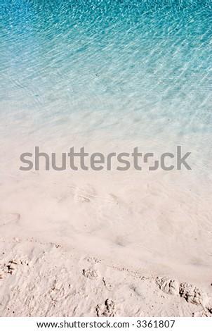 Calm aqua blue water ripples making reflections on a sandy beach - stock photo