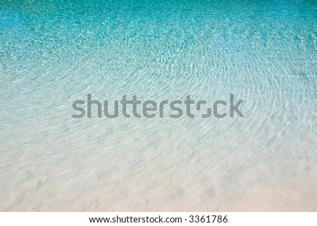 Calm aqua blue water ripples making reflections on a sandy white beach