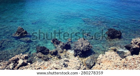 Calm blue sea and the rocks. Aged photo. Small bay near Cape Gelidonya. Vintage effect image. Rocky shore. Toned photo. Antalya Province, Turkey. Wide photo for site slider. - stock photo