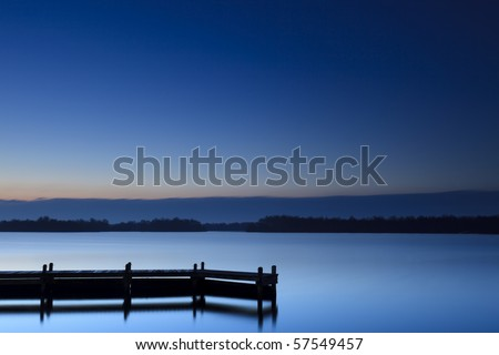 Calm blue sunset at a lake with jetty - stock photo