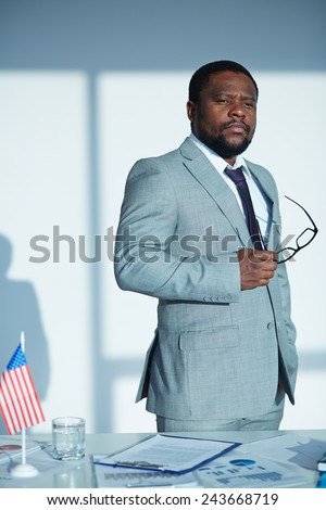 Calm businessman in suit holding eyeglasses - stock photo