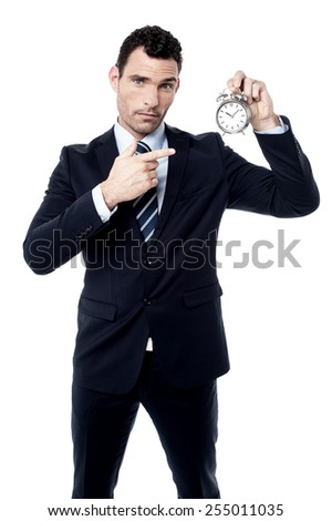 Calm businessman showing and pointing alarm clock - stock photo