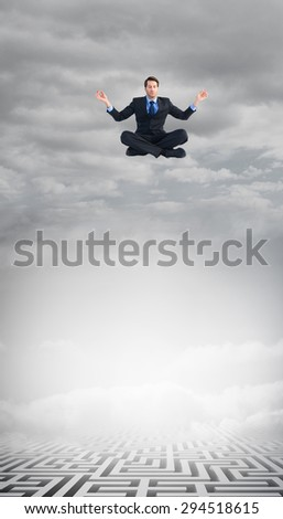 Calm businessman sitting in lotus pose against cloudy sky over maze