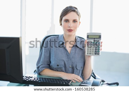 Calm businesswoman showing calculator sitting at her desk looking at camera - stock photo