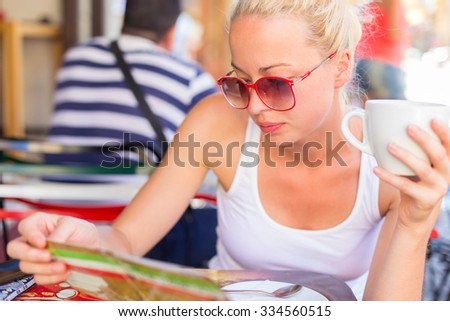 Calm casual blond lady wearing fashionable sunglasses, enjoying cup of coffee while checking menu in typical italian street coffee house or restaurant on warm summer day. - stock photo