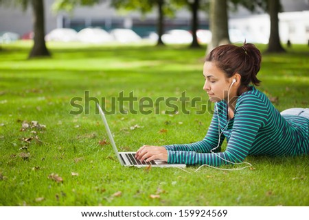 Calm casual student lying on grass using laptop on campus at college - stock photo