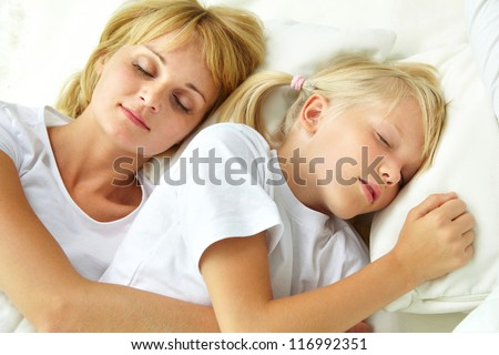 Calm child and her mother sleeping - stock photo