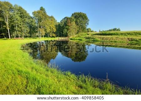 Calm countryside lake with a small bridge - stock photo