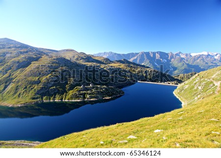 calm, dark cold mountain lake surrounded by rocky alpine mountain ranges and blue sky