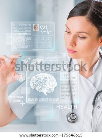 Calm doctor touching a medical interface in the hospital - stock photo
