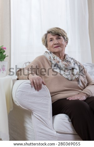 Calm elderly lady sitting alone in her room - stock photo