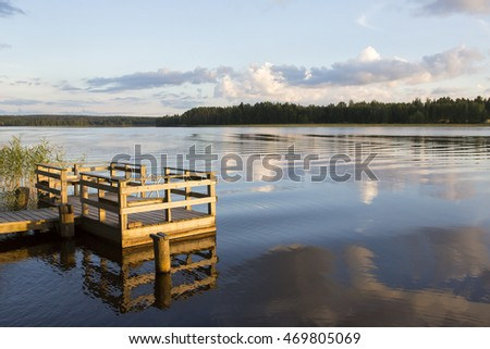 Calm evening during sunset in Finland. Still water makes perfect reflections of sky and forest. An empty pier is on the left where the focus point is.