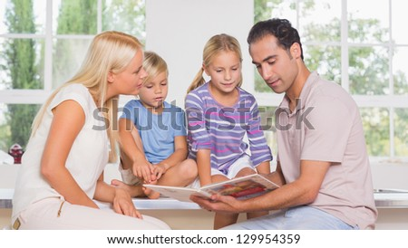 Calm family reading a story together in the kitchen