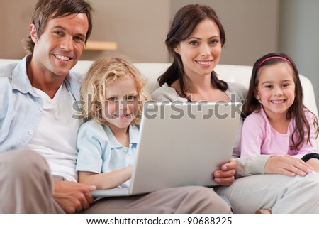 Calm family using a notebook in a living room - stock photo