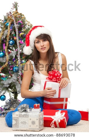 Calm female sitting near Christmas tree on the floor with many gifts, over white background - stock photo