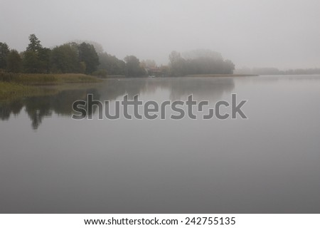 Calm foggy lake water surface during early morning, Mazury, Poland - stock photo