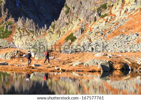 Calm glacier lake mirroring the mountain slope and passing hikers - stock photo