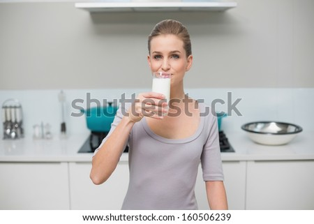 Calm gorgeous model looking at camera drinking glass of milk standing in kitchen - stock photo