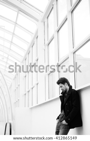 Calm handsome bearded man in coat looking down with hands in pockets - stock photo