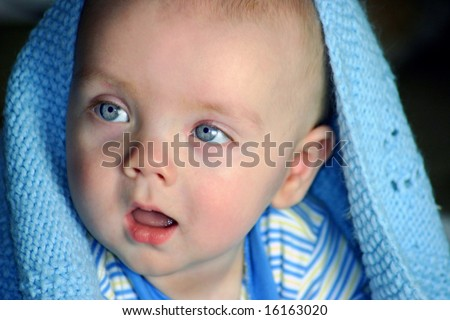 Calm, happy Baby with bright blue eyes under blanket - stock photo