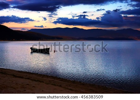 calm HDR sunset over the high mountain bulgarian lake, boat in foreground - stock photo