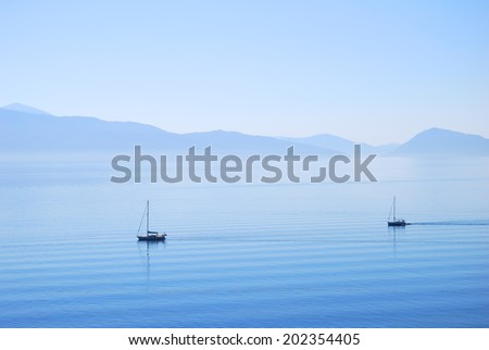 Calm ionian sea waters with sailing yachts and land in the distance - stock photo