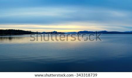 calm lake at night, sunset yellow light on blue sky reflections mountains, Magog Memphrémagog, Québec - stock photo