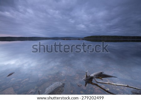 Calm lake at twilight, wood in the foreground, dalarna, sweden - stock photo