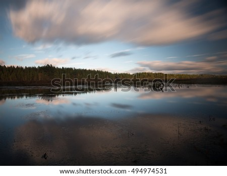 Calm lake in sweden photographed with long exposure, cloud reflections in the water