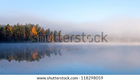 Calm lake panoramic landscape with fog in cold autumn morning - stock photo