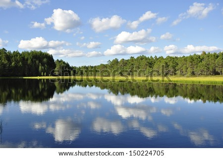 Calm lake reflection against the blue sky with white clouds - stock photo