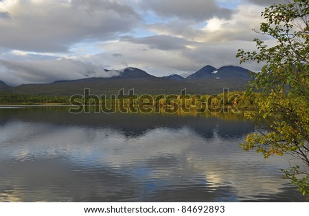 calm lake reflection and a cloudy sky, Abisko National park in Sweden.