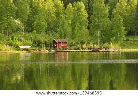Calm lake reflection in spring at sunset - stock photo