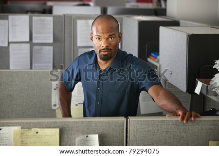 Calm Latino office worker standing in his cubicle - stock photo