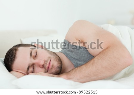 Calm man sleeping in his bedroom - stock photo