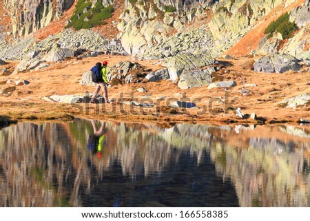 Calm mountain lake reflecting a pair of mountaineers passing along - stock photo