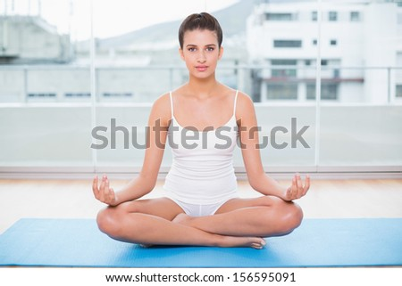 Calm natural brown haired woman in white sportswear practicing yoga in bright living room - stock photo