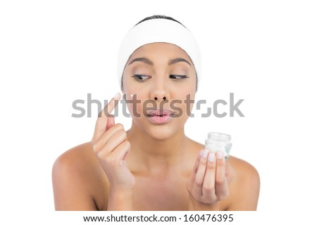Calm nude brunette using moisturizer looking at finger on white background