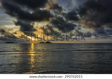 Calm ocean under dramatic sunset sky. - stock photo