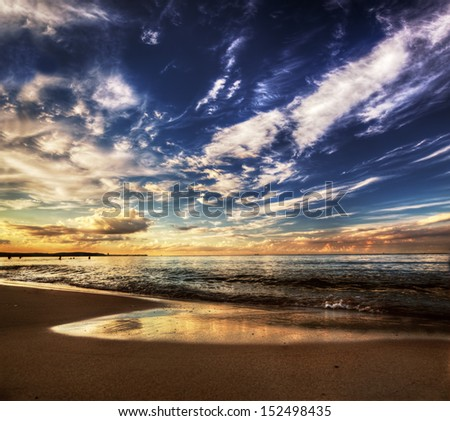 Calm ocean under dramatic sunset sky. Amazing cloudscape - stock photo