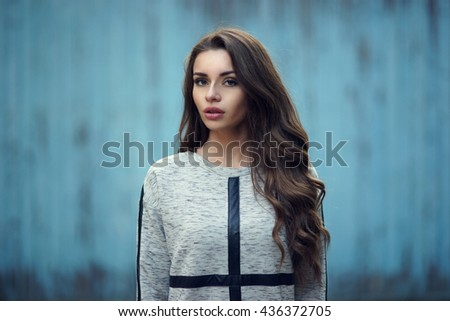 Calm or pensive girl portrait against blue old wooden wall. Pretty stylish fashionable woman in gray hoody with long curly hair looking at you. Shallow DOF, blurred background - stock photo
